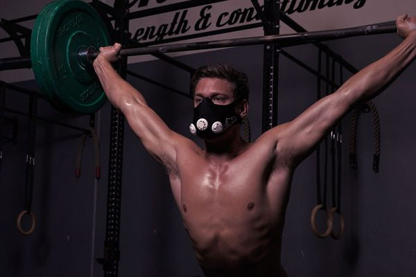 a man lifting weights wearing an altitude training mask